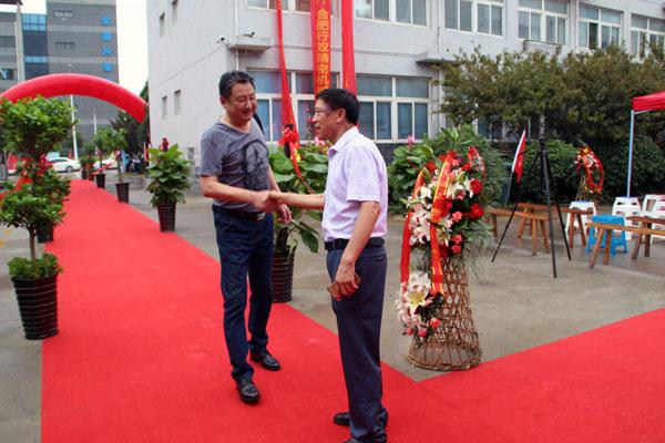 骆董站在红地毯上喜迎每一位宾客到来,瞧,他正在和合肥杰达物资公司陈军总经理握手迎接!