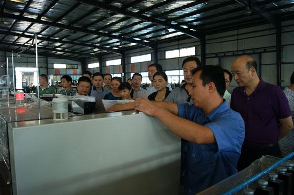 杏花印務公司總經理黃勝龍(圖右一)正在邢總的介紹下認真觀看設備運行情況