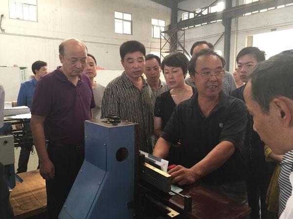 華生鑫公司技術人員正在向杏花印務技術骨干們介紹書刊后道裝訂機械使用和性能